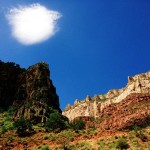 A solitary cloud hovers over shadow-cast Redwall Limestone on Grand Canyon National Park's Bright Angel Trail
