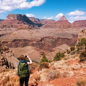 A hiker photographs Vishnu Temple and Wotan's Throne from Horseshoe Mesa